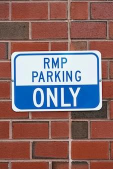 Señal de estacionamiento en primer plano de la pared de ladrillo