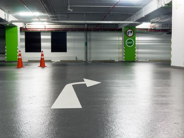 Señal de giro a la derecha y señal de salida atrapado en pilares verdes y marque el giro a la derecha en el estacionamiento.