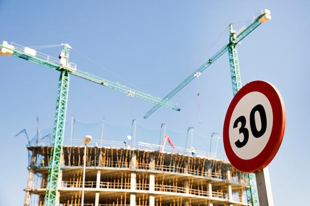 Señal de límite de velocidad 30 en frente del sitio de construcción contra el cielo azul