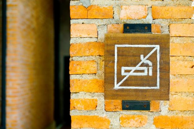 Señal de no fumar en la pared de ladrillo