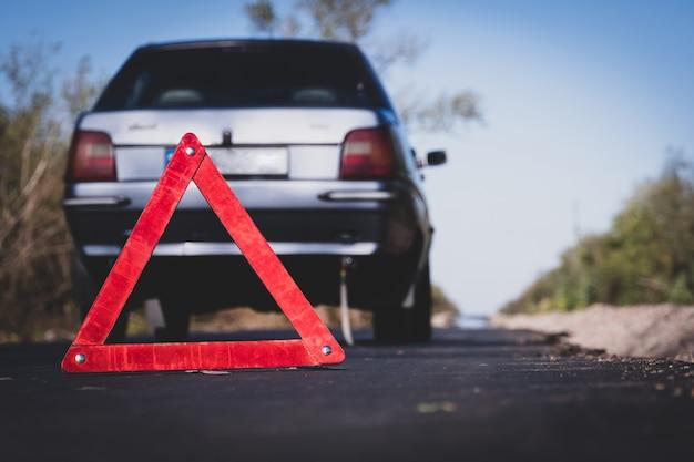 Señal de parada de emergencia roja de cerca en la carretera con el telón de fondo de un coche destrozado gris