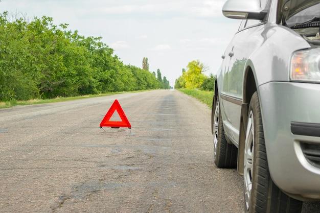 Señal de parada de emergencia roja y coche plateado roto en la carretera