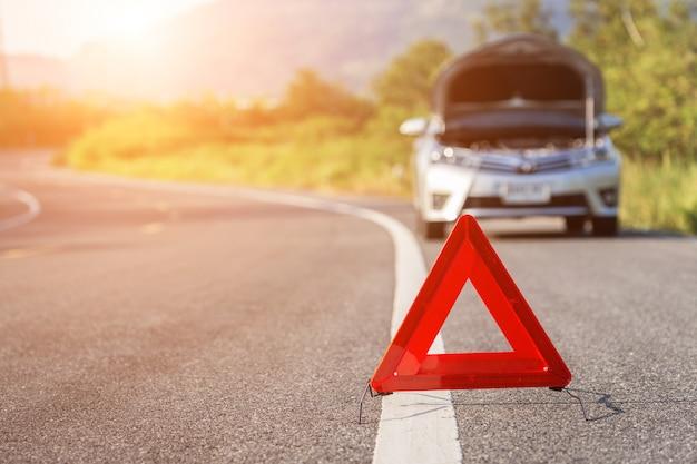 Señal de parada de emergencia roja y coche roto en la carretera