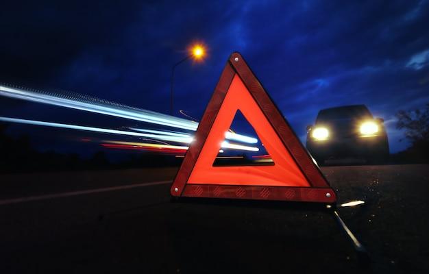 Señal de parada de emergencia roja con larga exposición de senderos de semáforo en la noche.