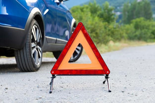 Una señal de parada de emergencia de un vehículo está instalada en la carretera, al lado del automóvil. copie el espacio.