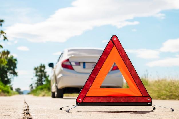 Señal de paro de emergencia y coche roto en carretera.
