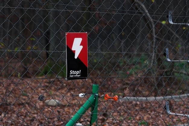 Señal de peligro en la rejilla metálica en bosque