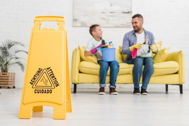 Señal de piso mojado con padre e hijo desenfocado