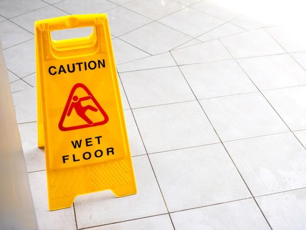Señal de precaución de piso mojado en una pasarela cerca del edificio después de llover