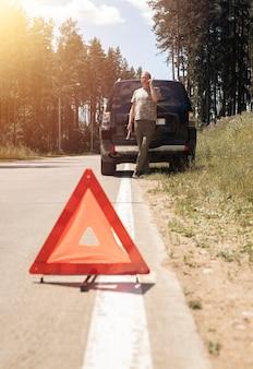 Señal de precaución del triángulo rojo en la carretera después de la rotura del coche en un viaje por carretera y el conductor habla en una llamada de teléfono celular ...