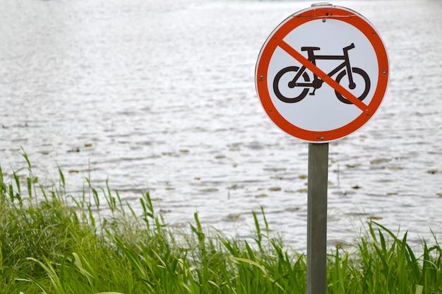 Señal de prohibición de bicicletas sobre fondo de agua en un parque