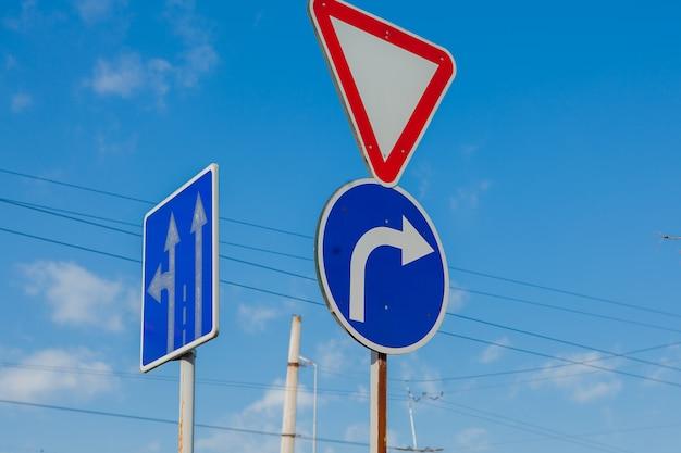 Una señal que muestra el camino y gira solo a la derecha al fondo de un cielo azul brillante