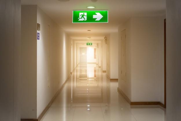 Señal de salida de emergencia verde en hotel que muestra el camino para escapar