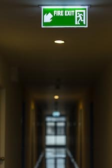 Señal de salida de fuego verde en el pasillo del hotel
