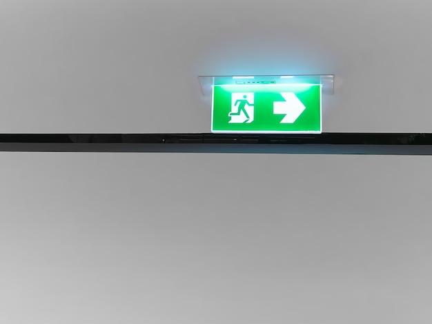 Señal de salida de incendios iluminada en blanco en el panel verde debajo del techo