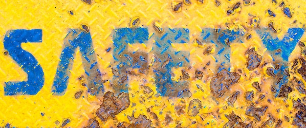 Señal de seguridad amarilla con fondo de textura oxidada
