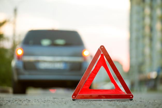 Señal de stop triángulo rojo de emergencia y coche roto en una calle de la ciudad.