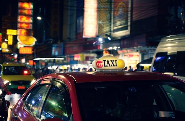 Señal de taxi con luces desenfocadas desenfoque en chinatown en bangkok en la noche, tailandia, el sudeste asiático