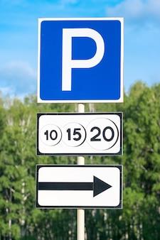 Señal de tráfico de estacionamiento pagado con flecha de dirección de movimiento