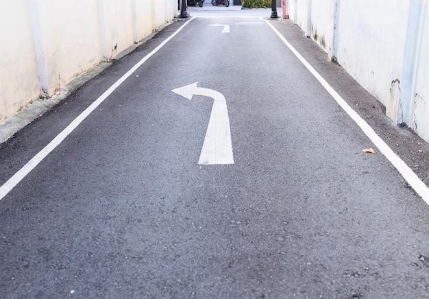 La señal de tráfico de la flecha blanca gira a la izquierda hacia la carretera principal y las líneas de sendero blancas en la carretera asfaltada en el callejón