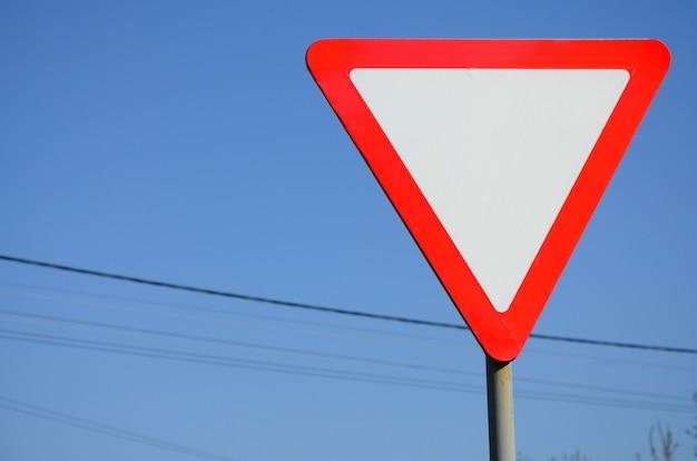 Señal de tráfico en forma de un triángulo blanco. ceda el paso