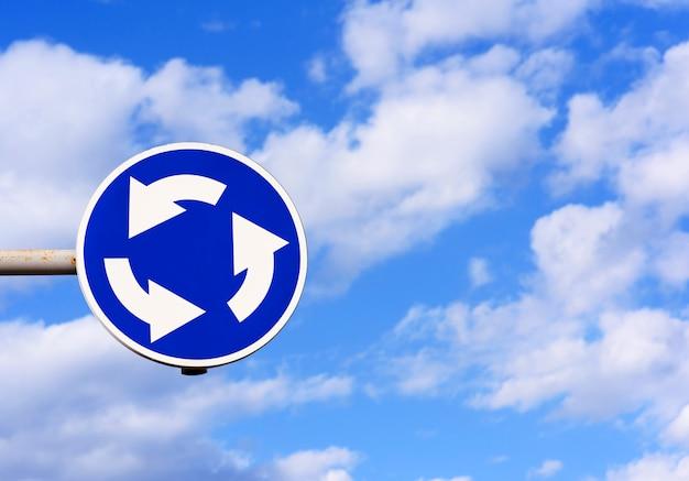 Señal de tráfico movimiento circular en el cielo azul