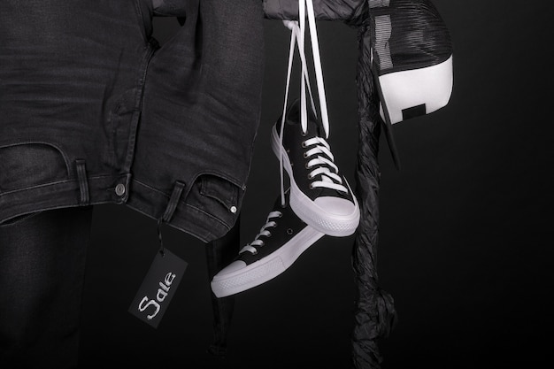 Señal de venta. snakers en blanco y negro, gorra y pantalón, jeans colgando de perchero sobre fondo negro. viernes negro.