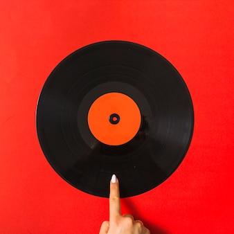 Señalando el dedo en el disco de vinilo sobre fondo rojo