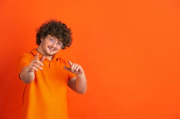 Señalando, eligiéndote. retrato monocromático del hombre joven caucásico en la pared anaranjada. hermoso modelo masculino rizado en estilo casual.