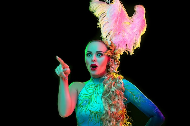 Señalando. hermosa mujer joven en carnaval, elegante disfraz de mascarada con plumas en pared negra en luz de neón. copyspace para anuncio. celebración de fiestas, baile, moda. tiempo festivo, fiesta.