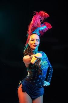 Señalando. hermosa mujer joven en carnaval, elegante disfraz de mascarada con plumas sobre fondo negro en luz de neón. copyspace para anuncio. celebración de fiestas, baile, moda. tiempo festivo, fiesta.