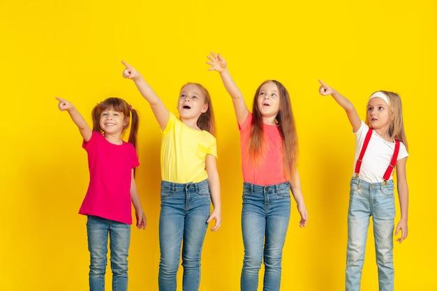 Señalando. niños felices jugando y divirtiéndose juntos sobre fondo amarillo de estudio. los niños caucásicos con ropa brillante se ven juguetones, riendo, sonriendo. concepto de educación, infancia, emociones.