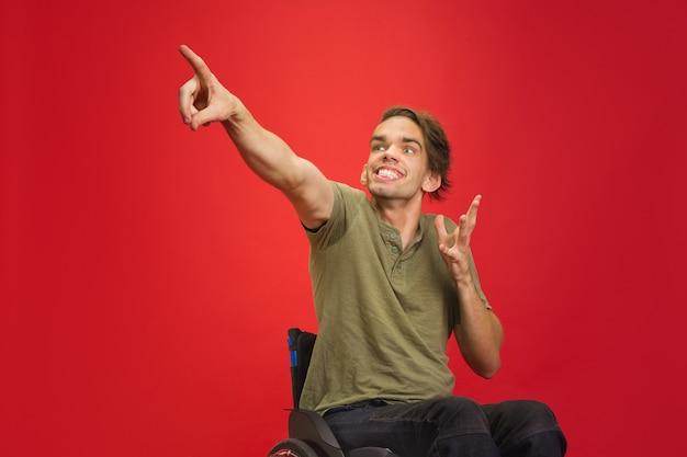 Señalando el retrato del hombre discapacitado joven caucásico aislado en la pared roja del estudio