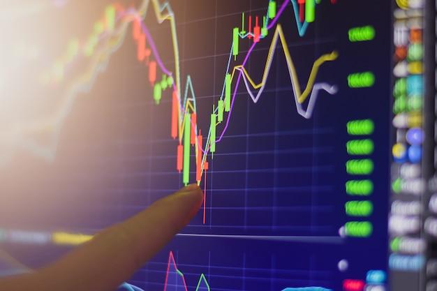 Señalar con el dedo en la bolsa de valores gráfico de comercio de inversión