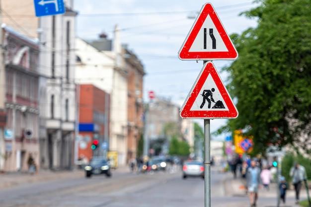 Señales de advertencia sobre reparaciones en la calle en un primer plano de fondo urbano borroso