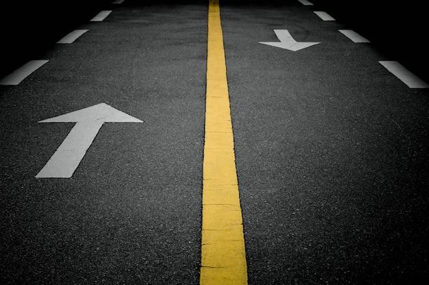 Señales de flecha blanca hacia adelante en la carretera
