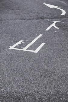 Señalización de tráfico blanco sobre asfalto