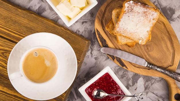 Sencillo desayuno de productos tradicionales: tostadas con mantequilla y mermelada de frambuesa.