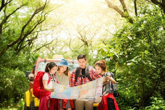 Senderismo - excursionistas mirando el mapa. pareja o amigos navegando juntos sonriendo feliz durante la excursión de camping al aire libre en el bosque. joven mujer de raza mixta asiática y el hombre.
