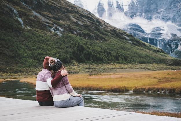 Senderismo joven pareja viajero sentado y mirando hermoso paisaje
