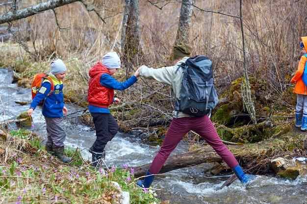 Senderismo madre ayuda a los niños a cruzar el arroyo de montaña. familia deportiva con mochilas