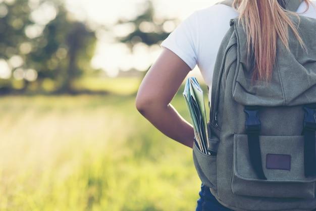 Senderismo mujer con mochila caminando por un camino de ripio