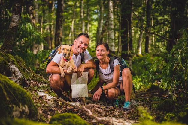 Senderismo pareja con perro posando en el bosque