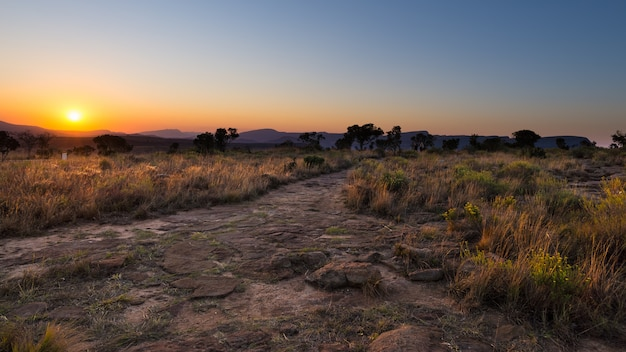 Sendero de hormigón que conduce al mirador blyde river canyon, famoso destino turístico en sudáfrica. luz puesta del sol escénica en las cordilleras.