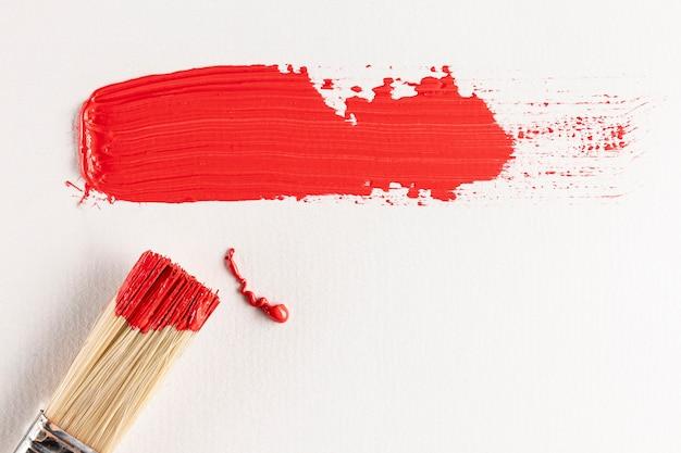 Sendero de pintura roja con pincel