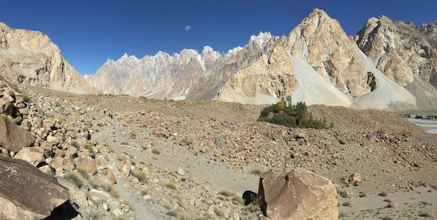Sendero de trekking en passu muestran la forma de relieve de la sequía y las montañas cubiertas de nieve.