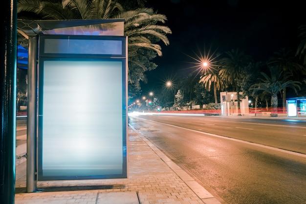 Senderos de luz para autos de carretera en la caja de luz de publicidad de la ciudad moderna