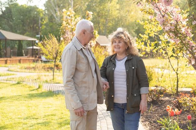 Senior anciano caucásico pareja juntos en el parque en primavera o verano. esposa abrazando marido sonríe con felicidad. hermosa relación de amor y cuidado de la jubilación de las personas mayores.
