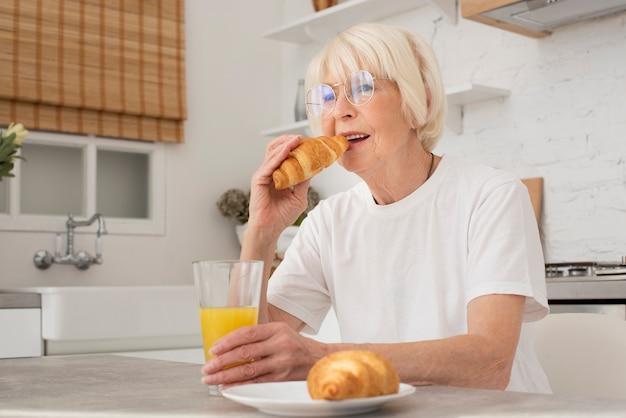 Senior comiendo un croissant en la cocina