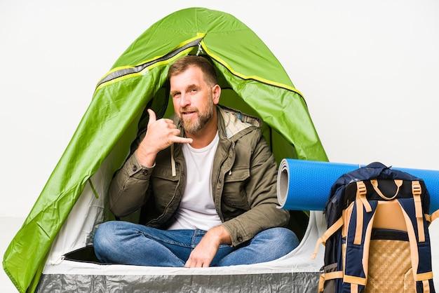 Senior dentro de una carpa aislada en blanco mostrando un gesto de llamada de teléfono móvil con los dedos.